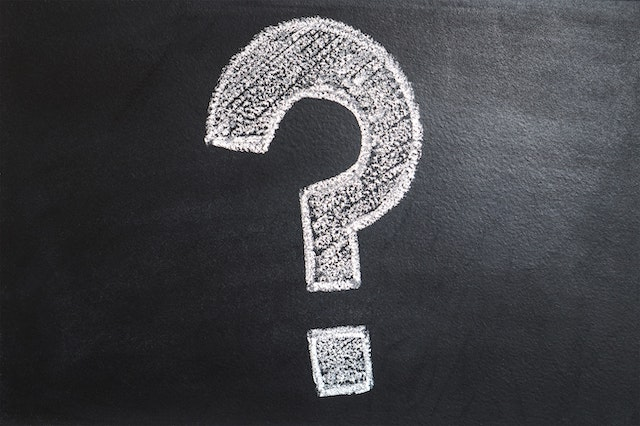 A black chalkboard with a big white question mark in chalk.