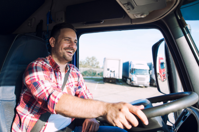 A man wearing a red plaid shirt is driving a truck while smiling.