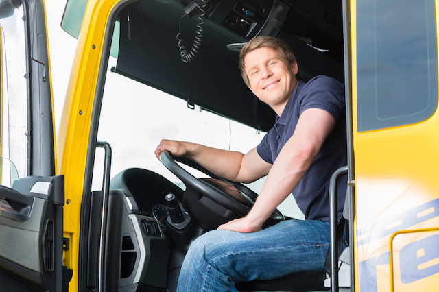 A man with blonde hair, wearing a navy blue polo shirt and jeans, is sitting in the driver's seat of a large commercial truck