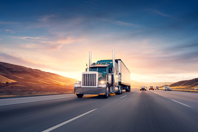 An eighteen wheeler truck is driving down a highway at sunset