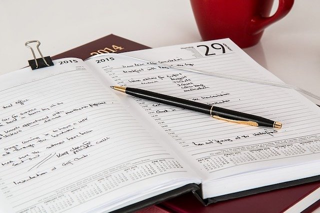 A pen rests on an open planner