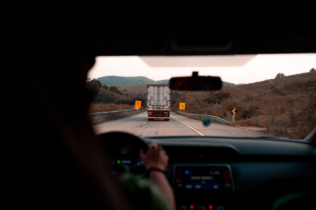 A view from behind a truck driver, looking out the windshield. Outside there is another truck on the road ahead with a hilly landscape in the background.