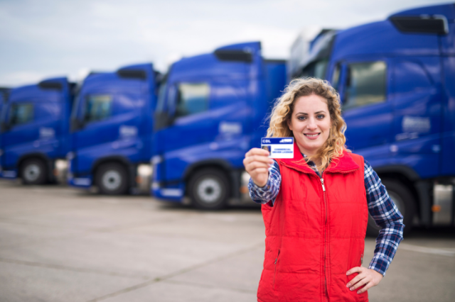 A woman standing in front of 4 large trucks is holding up her CDL license.